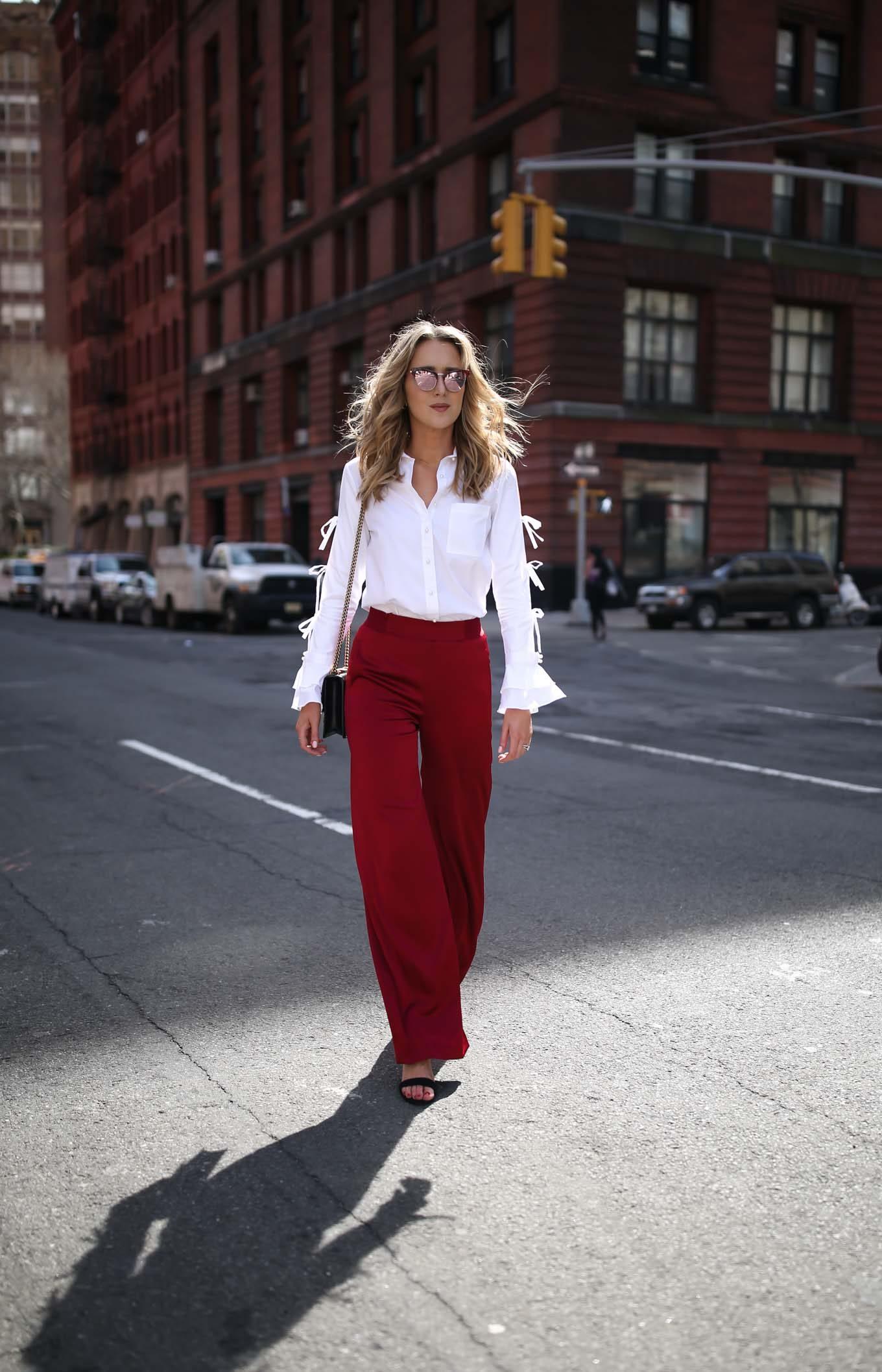 Z czym nosić czerwień? Jakie kolory pasują do czerwieni? biała koszula z kokardkami czerwone spodnie
